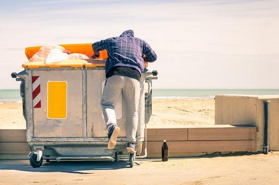 Mann an Mülltonne