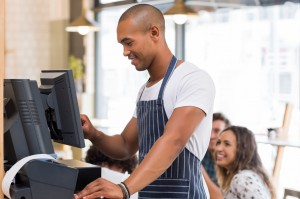 Happy young waiter in blue apron checking bill before printing it. Young african waiter printing bill in cafeteria. Waiter printing order on digital cash register.