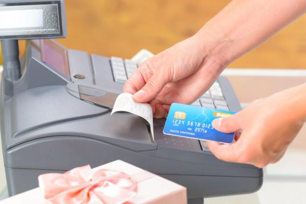 Eine Registrierkasse wird von einem Verkäufer bedient