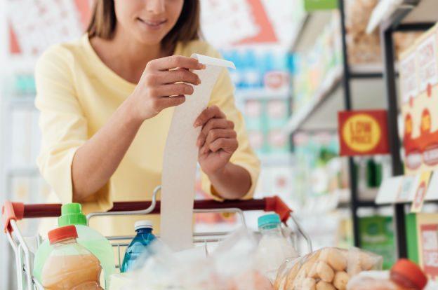 Frau kontrolliert Kassenbon beim Einkaufen im Supermarkt