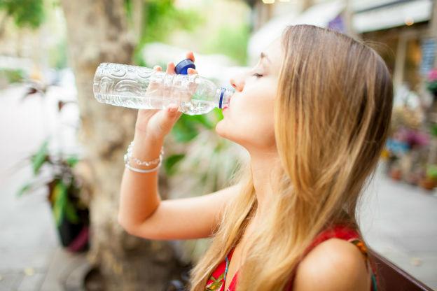Junge Frau trinkt aus einer Plastik-Trinkflasche