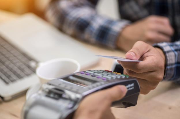 Person bezahlt kontaktlos mit der Kreditkarte