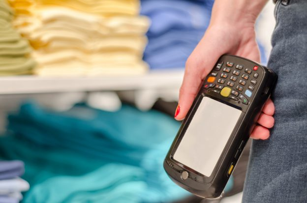 Ein Hand, die einen mobilen Etikettendrucker hält - vor einem verschwommen Warenregal im Hintergrund.