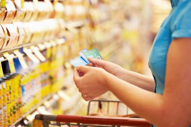 Eine Frau vor einem Lebensmittelregal und Rabbatcoupons in der Hand