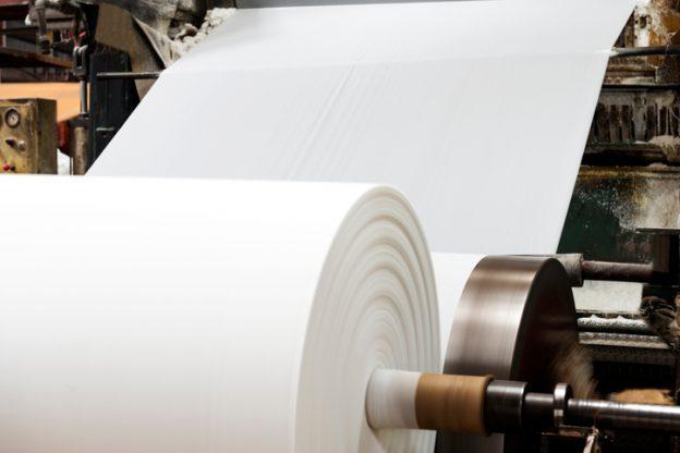 Produktion von Papier, das zu einer großen Papierrolle aufgerollt wird.