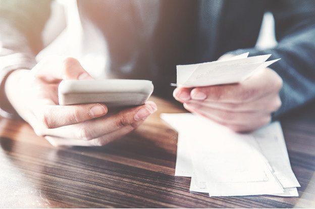 Eine Person, die mithilfe eines Smartphones ihre Kassenzettel digital verwaltet