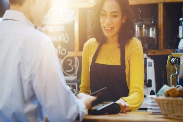 Mann möchte am Tresen eines Cafés bezahlen