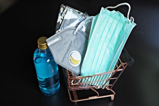 Mundschutz-Maske, Desinfektionsmittel und weitere Hygieneartikel liegen im Einkaufswagen