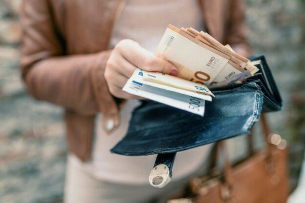 Frau holt Bargeld aus ihrem Portemonnaie