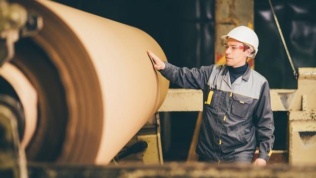 Ein Mitarbeiter einer Papierfabrik begutachtet die Papierrolle